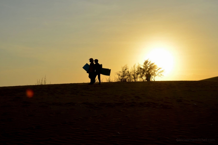 A pair of people holds plastic sandboards at Mui Ne, Vietnam's Red Sand Dunes.