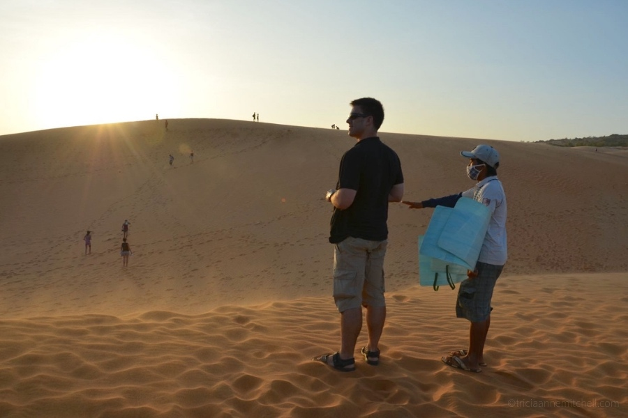 People sandboarding on Mui Ne's Red Dunes.