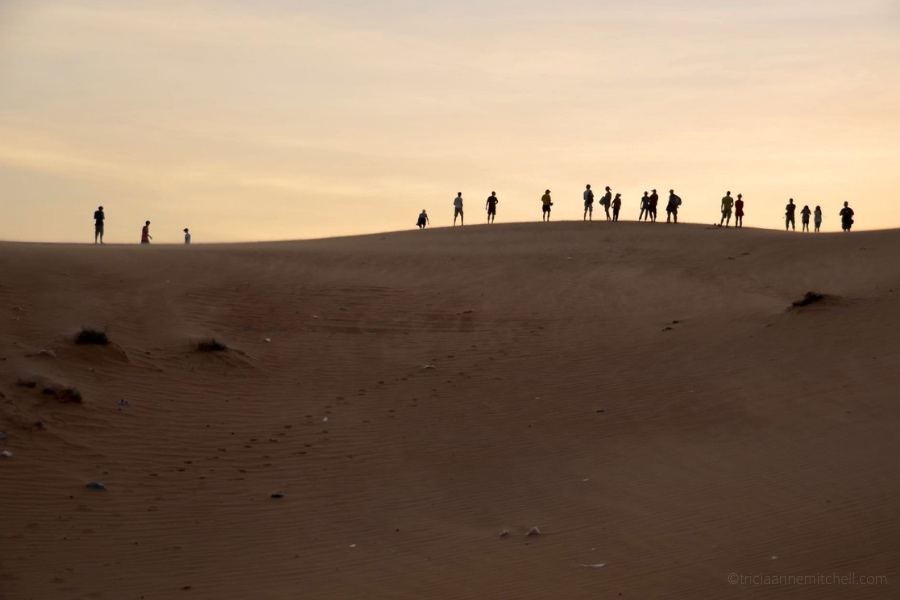 Silhouetted human figures stand on top of Mui Ne's Red Sand Dunes.