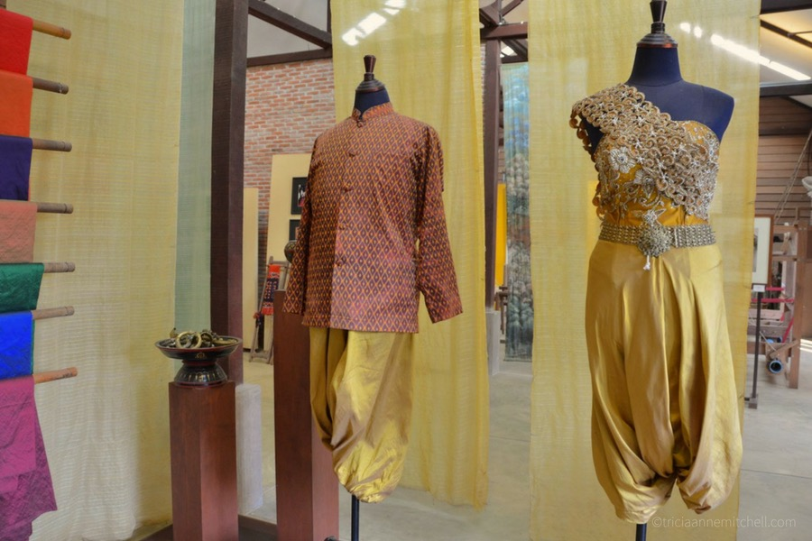 Two traditional Khmer outfits — one for men, and another for women — hang in the Artisans d'Angkor showroom.