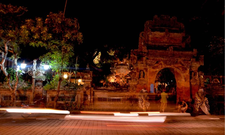 Motorcycles and cars drive past Udud's Royal Palace at night.