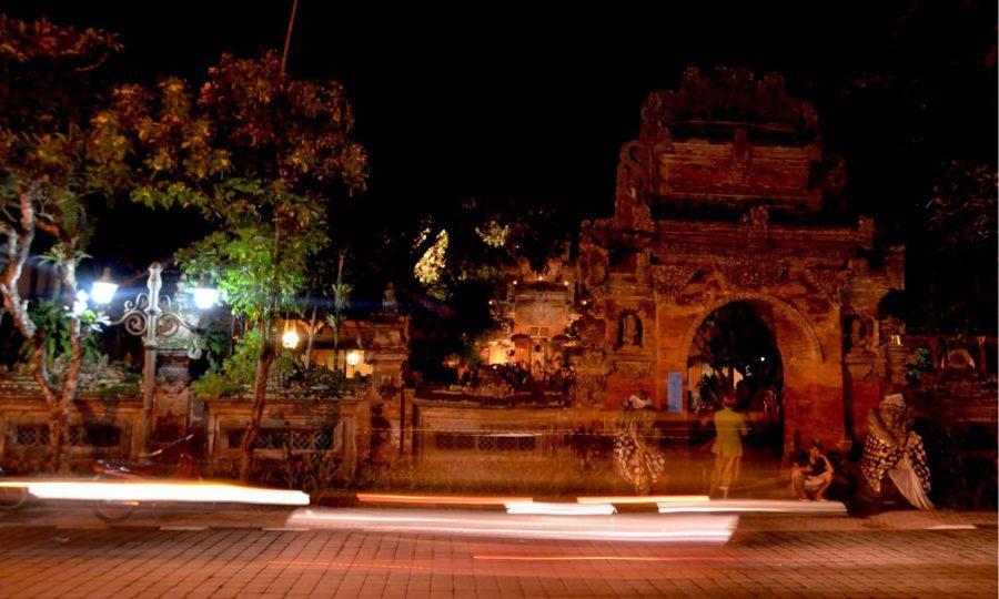 Motorcycles and cars drive past Udud's Royal Palace at night.