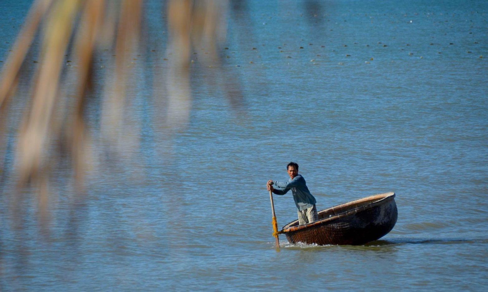 A man paddles a Vietnamese basket boat through the water near Mui Ne.