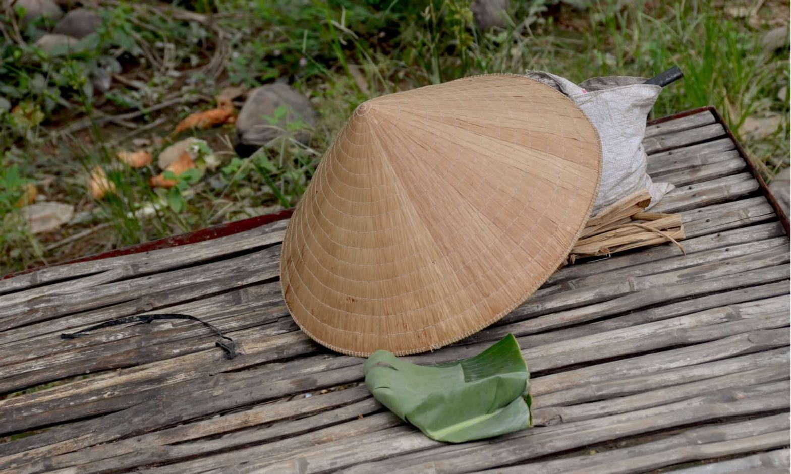 A traditional Vietnamese hat - known as Nón Lá - rests on an outdoor table in Vietnam.