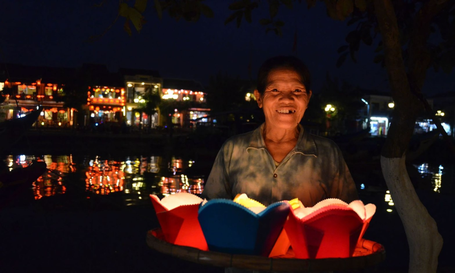 A woman holds a tray of red and blue paper lanterns for sale, in Hoi An, Vietnam.