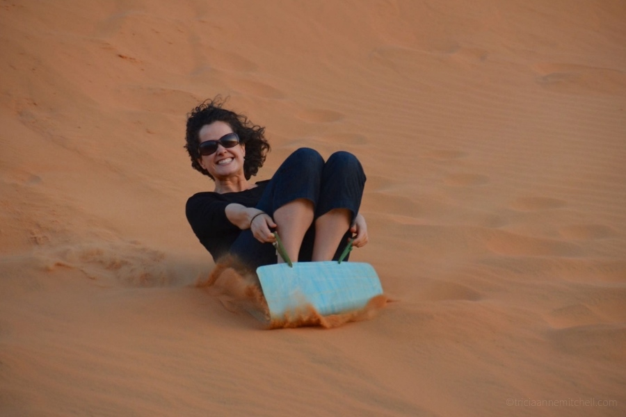 A woman slides down Mui Ne's Sand Dunes in Vietnam.