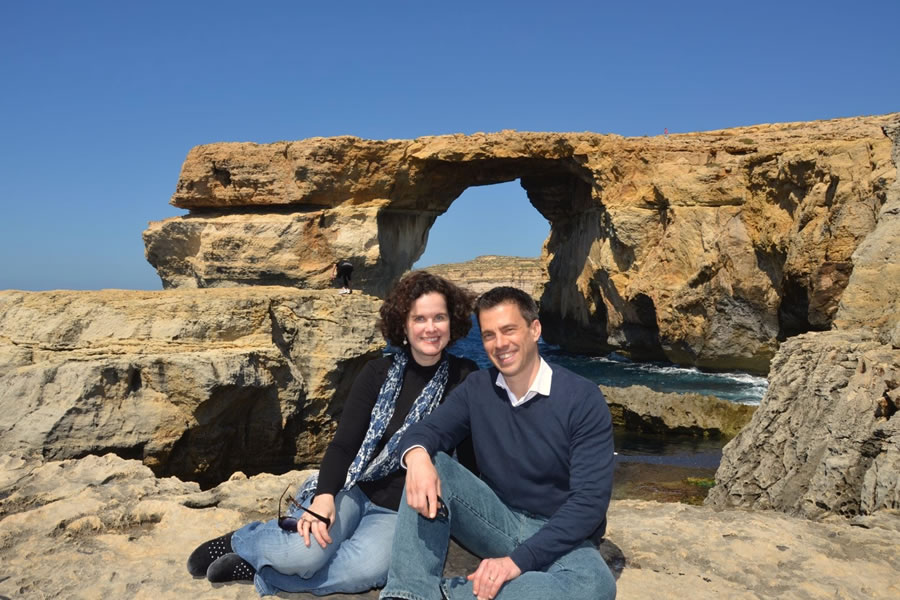 A couple sitting in front of the Azure Window on the Maltese island of Gozo.