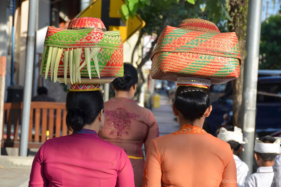 Balinese women carry baskets on their heads containing spiritual offerings.