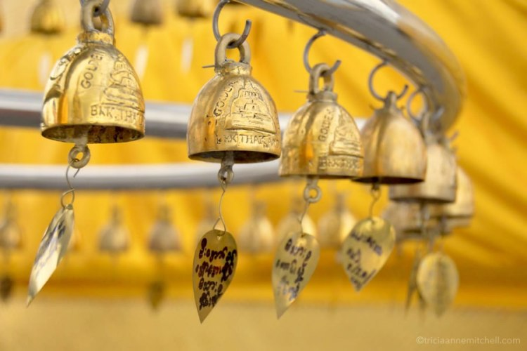Golden bells with messages handwritten on them hang at Bangkok's Golden Mount Temple.
