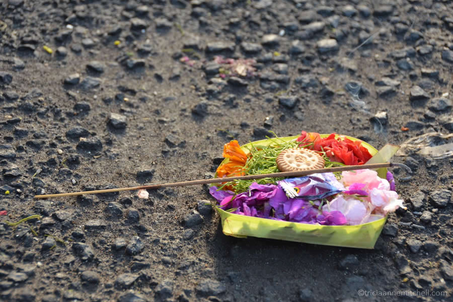 A Balinese spiritual offering (flowers, incense and a cookie) sits on the pavement in Jimbaran.