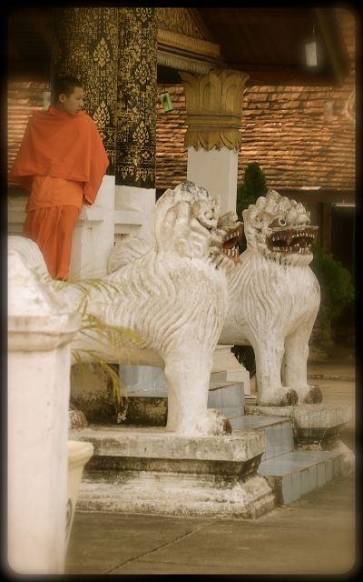 A young monk, dressed in an orange robe, sits on a balcony beside white statues of lion-like figures.