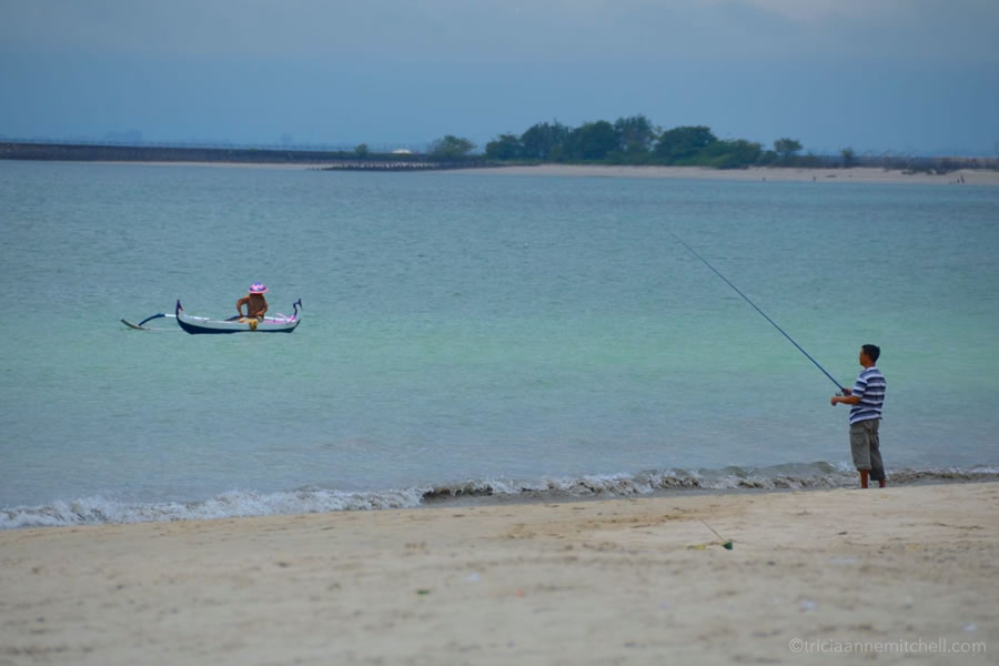 Two men fish in Jimbaran, Bali. One is in the boat, another is on the beach.