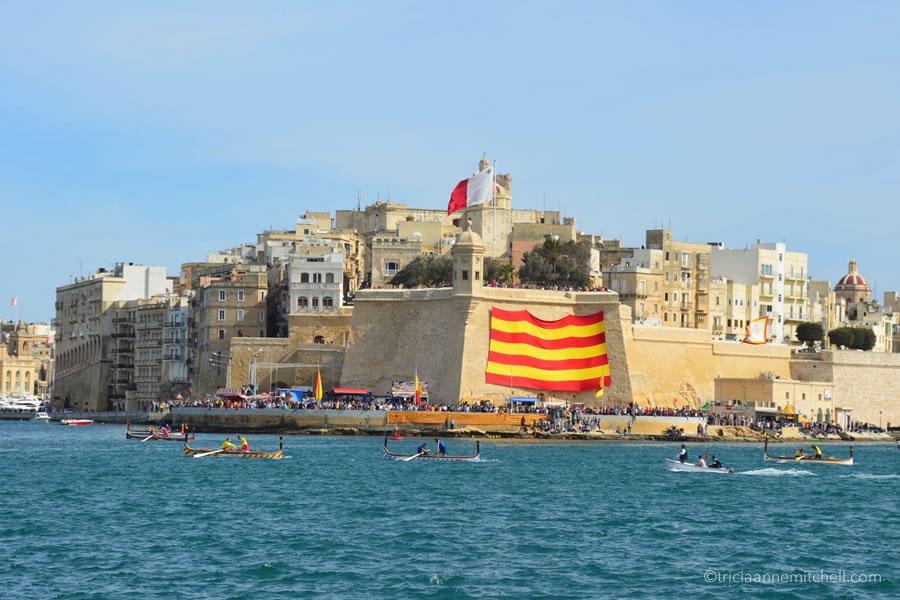Freedom Day regatta participants race in a gondola-like boat called a dgħajsa, in Malta's Grand Harbour.