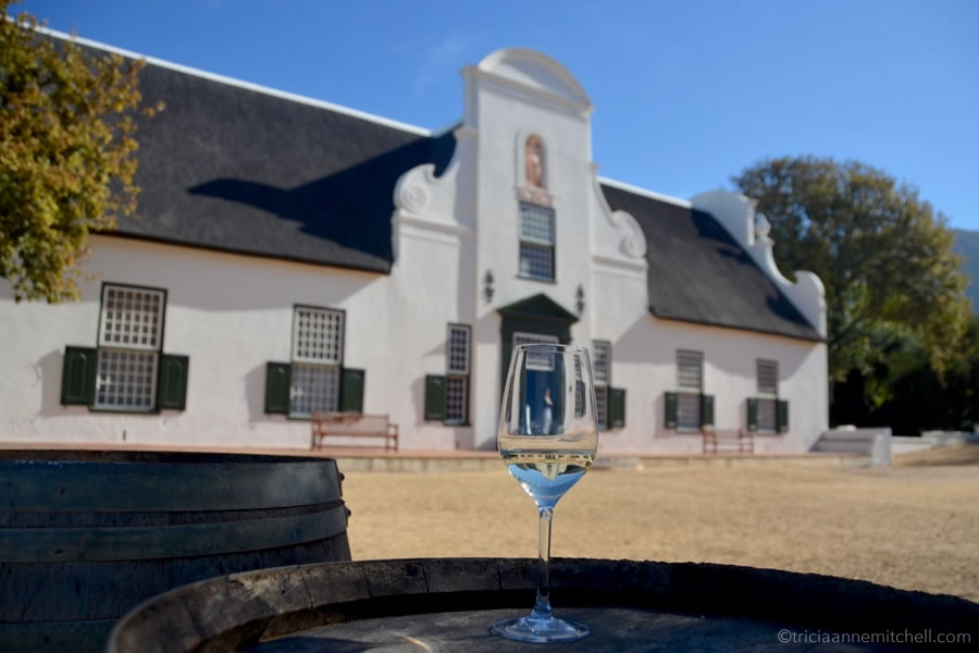 A wine glass sits on a barrel in front of Groot Constantia Winery in South Africa.