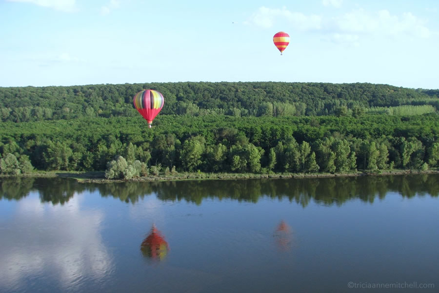 Two multicolored hot air balloons flying over France's Loire Valley.
