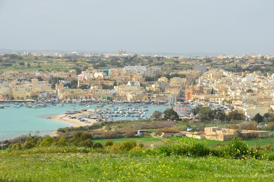 Marsaxlokk Harbour is seen from afar, with a green field in the foreground.