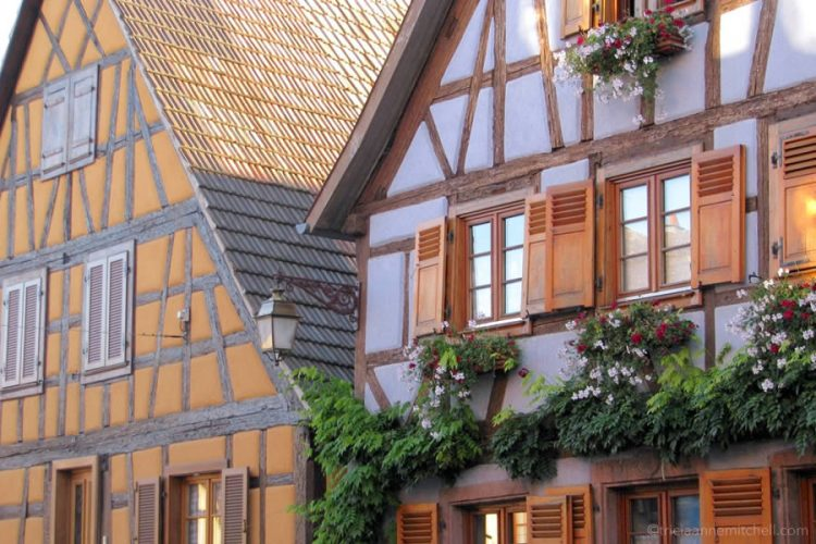 A golden home and a lavender neighboring building in the French village of Saint Hippolyte.