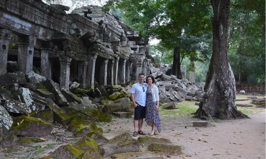 A couple, standing in front of the Ta Prohm Temple in Cambodia, which is overgrown by trees.