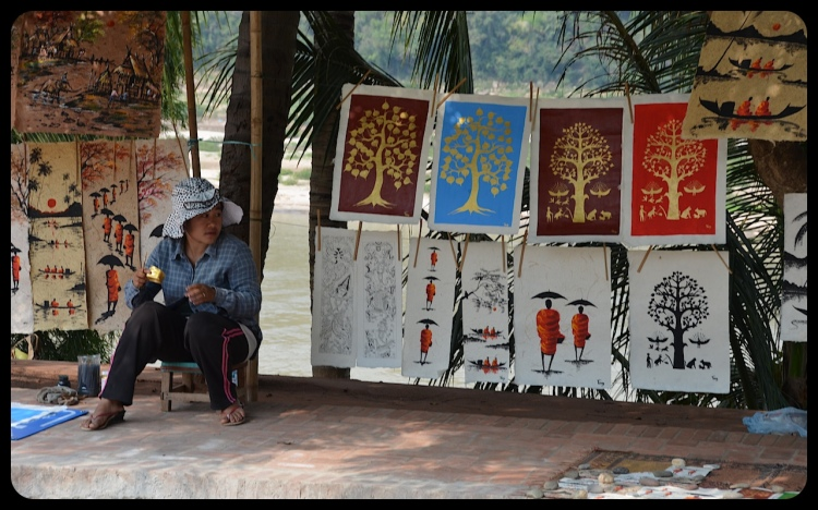 A woman, selling Buddhist-themed artwork, looks on from a sidewalk in Luang Prabang, Laos.