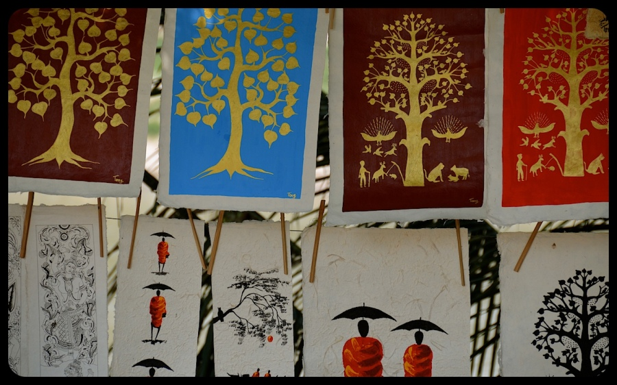 Artwork, hanging for sale depicts golden trees and monks.