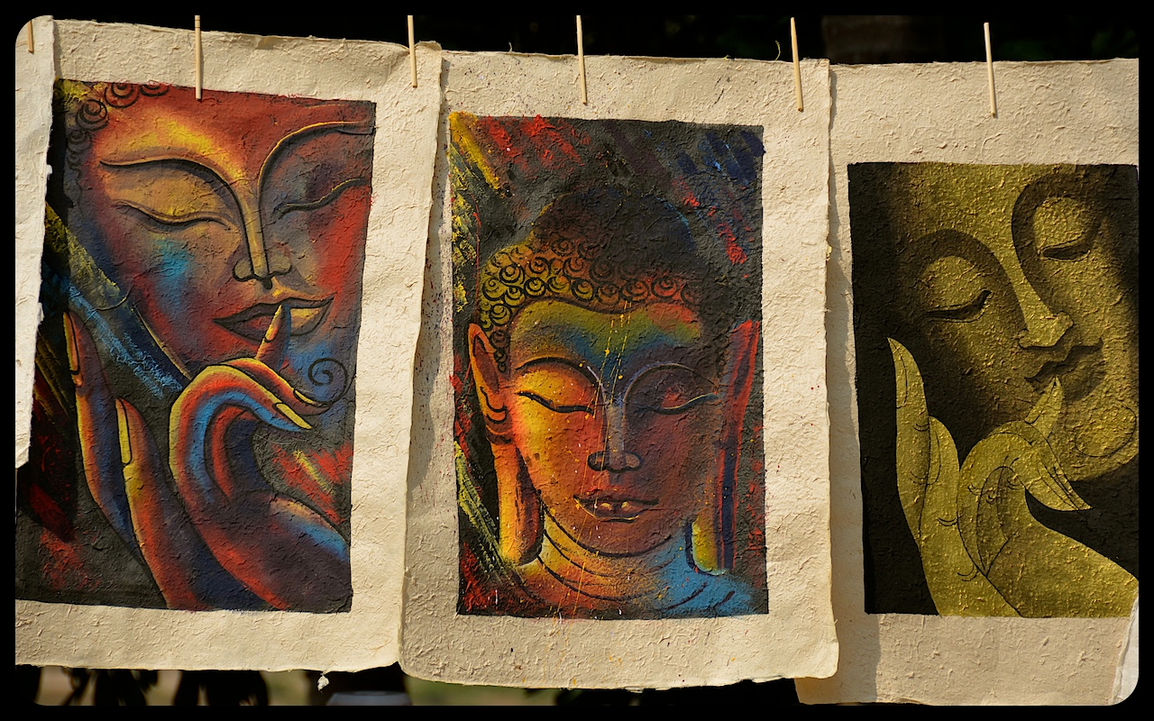 Images of Buddha, painted on hand-made paper, hang for sale at a stand in Luang Prabang, Laos.