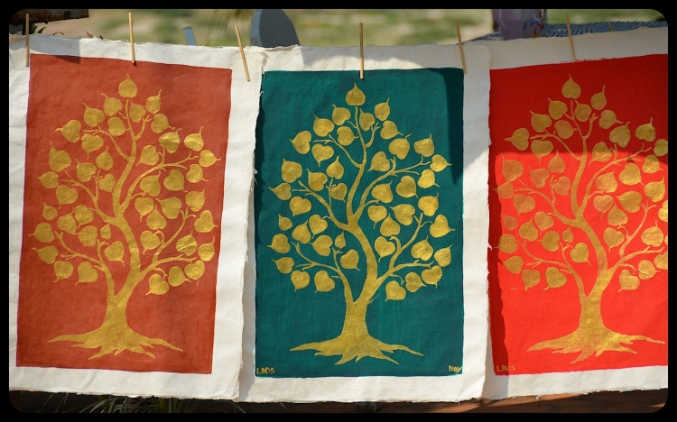 Street art hangs for sale on a street in Luang Prabang, Laos. The art is simple, with the silhouette of a golden tree painted on a solid background.