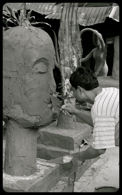 Man sculpting Buddha Statue in Laos
