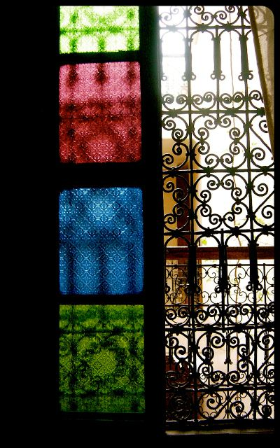 A vertical panel of green, red, and blue Moroccan glass fills a window. There is wrought ironwork on the right side of the frame.