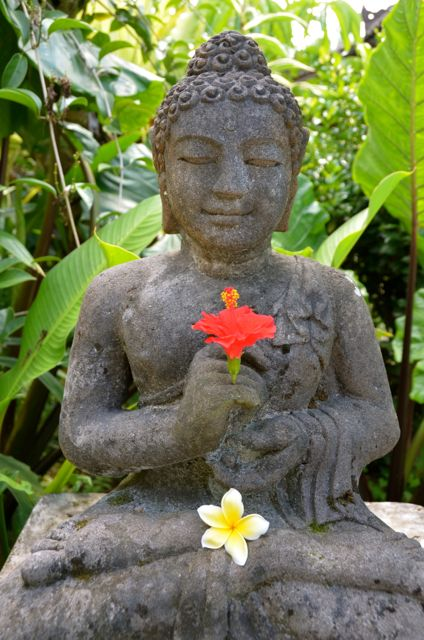 A Balinese Buddha statue holds a red hibiscus.