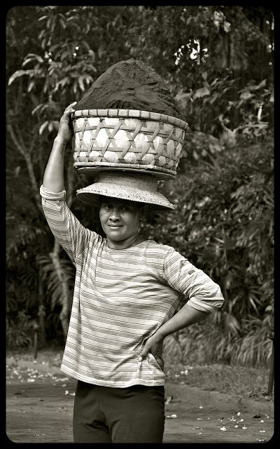 A woman carrying soil on her head in Ubud, Bali.