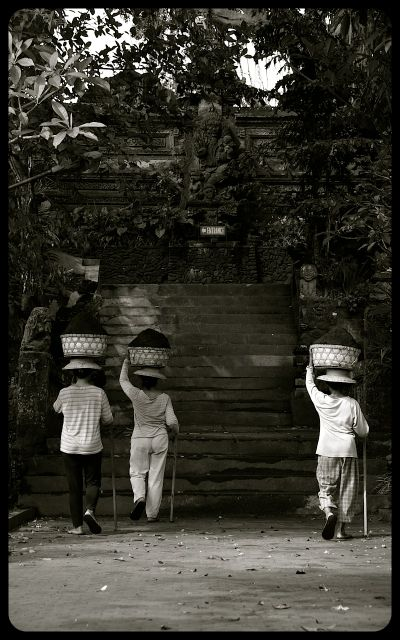 Three ladies carry baskets of soil on their heads in the Indonesian city of Ubud, on the island of Bali.