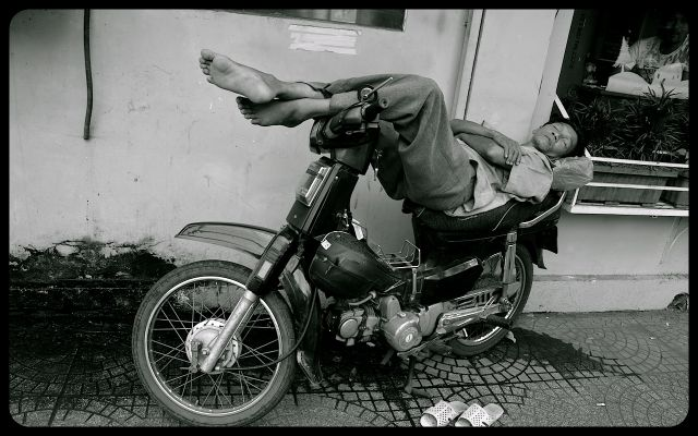 Man sleeping on motorbike in Ho Chi Minh photograph by Tricia Mitchell