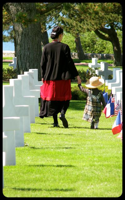 Mother and young girl walk among graves in Normandy cemetery