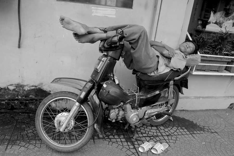 A nan naps on a motorbike in Ho Chi Minh City, Vietnam. His legs are propped on the handlebars.