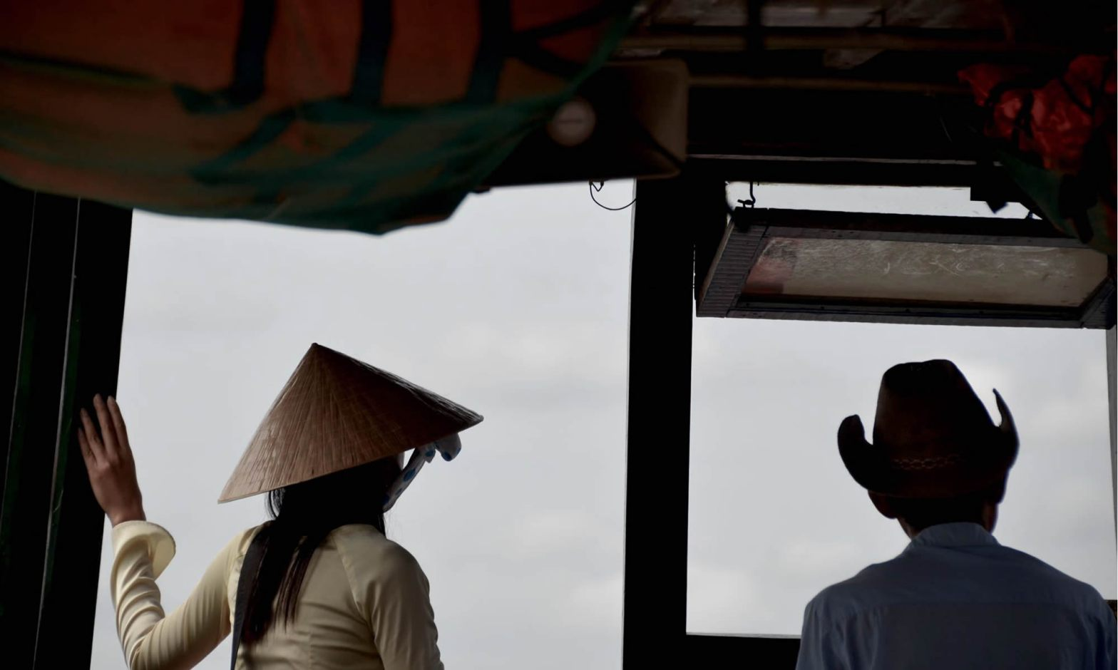 A woman wearing a traditional Vietnamese non la hat, stands next to a man in a cowboy hat.