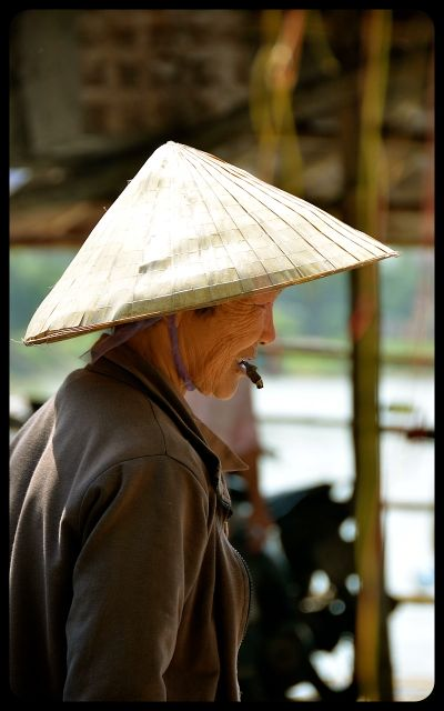 Woman smoking with non la hat in Hoi An Vietnam