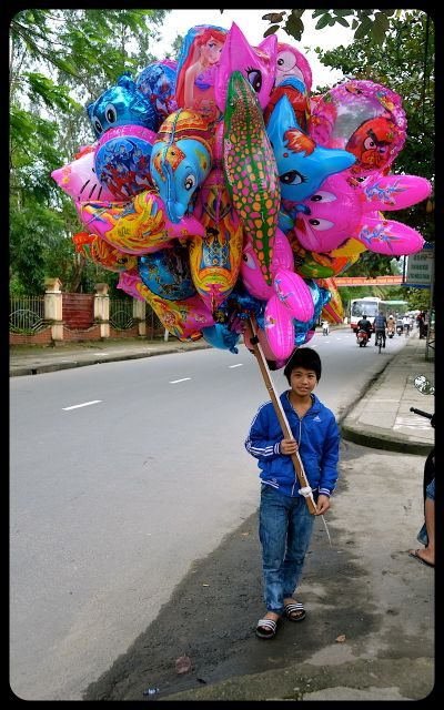 Boy carrying pink balloons for sale - Hoi An Vietnam