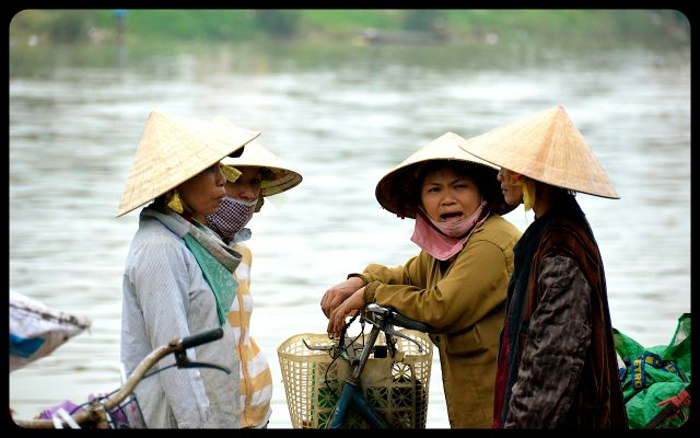 Women talking in Hoi An, Vietnam wearing non la hats on the riverside