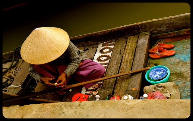 Woman cooking on a wooden boat in Hoi An Vietnam
