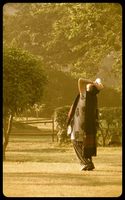 woman doing sun salutation in the Lodi Gardens - New Delhi, India
