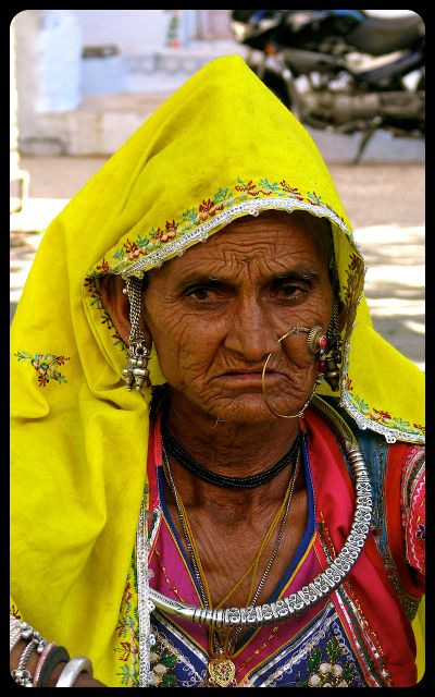 Woman wearing traditional jewelry and clothes selling vegetables in Pushkar, India