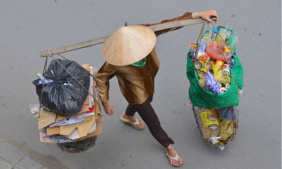 A Vietnamese woman, wearing a traditional hat, carries baskets of recyclables in Hoi An, Vietnam.