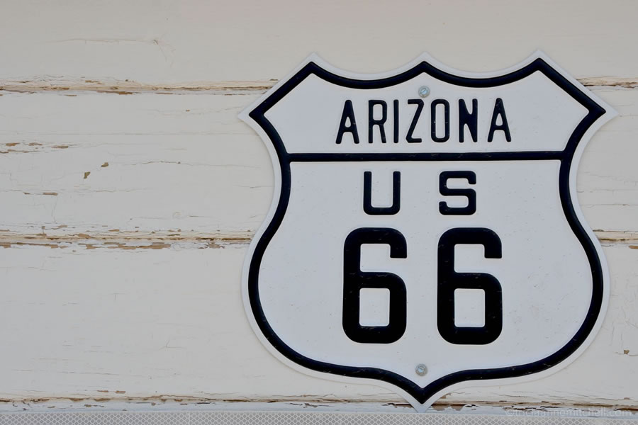 An Arizona Route 66 sign hanging on a white building.