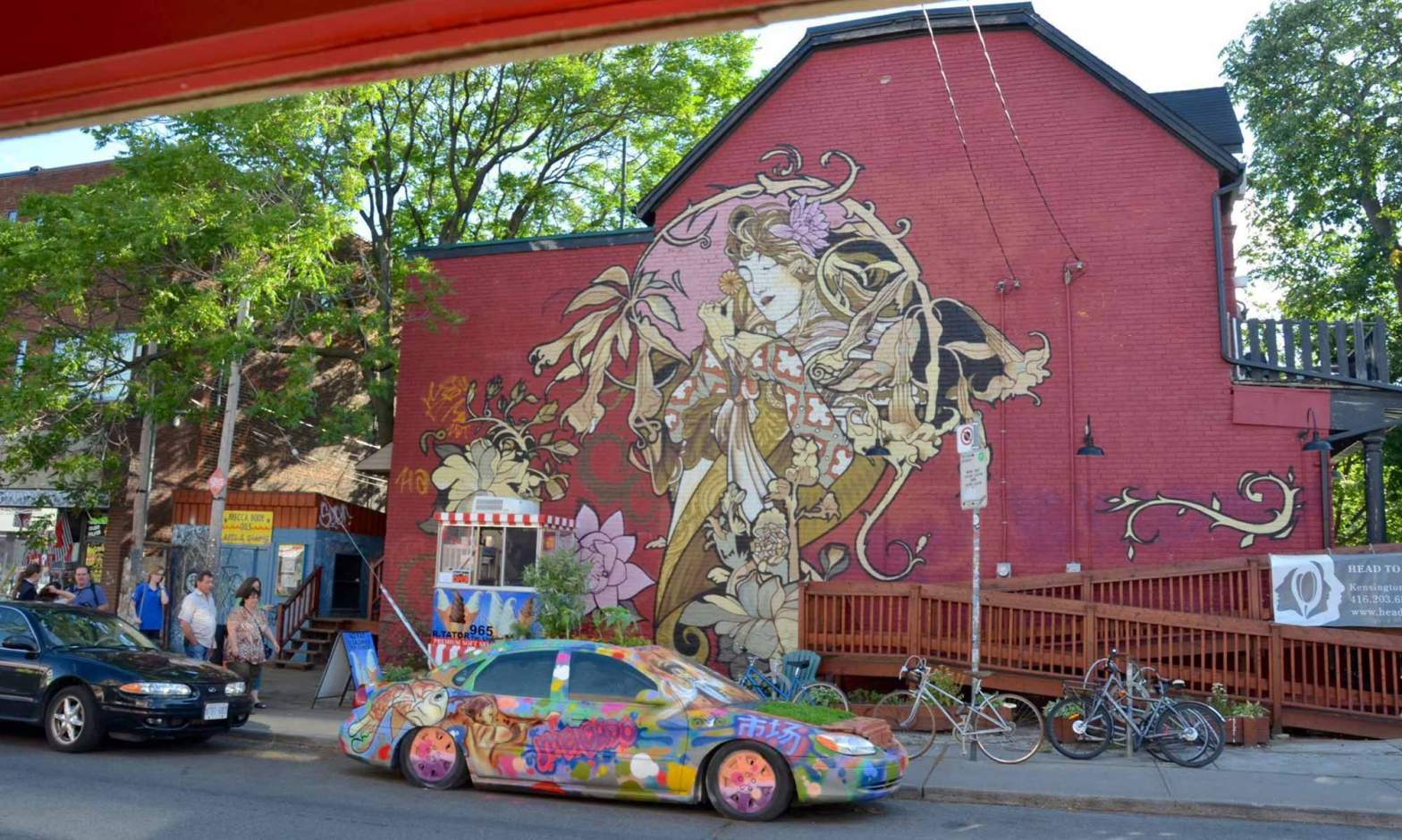 A mural of a woman is painted on a red building in the Kensington district of Toronto.
