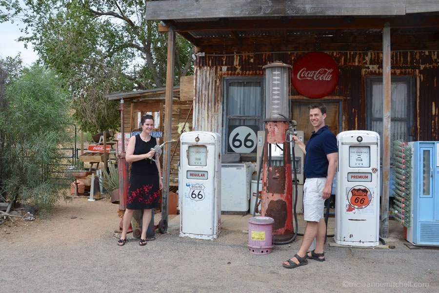 A man and a woman pretend they're pumping gas at a vintage-themed general store along Route 66, in Arizona.