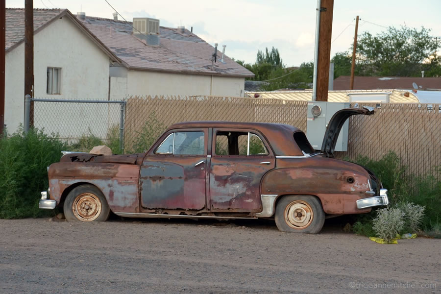 A rusted and abandoned car sits on the side of Route 66 in Holbrook, Arizona.