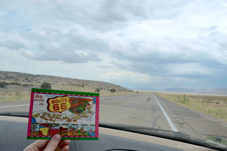 A hand holds a Route 66 postcard in front of a car's windshield.