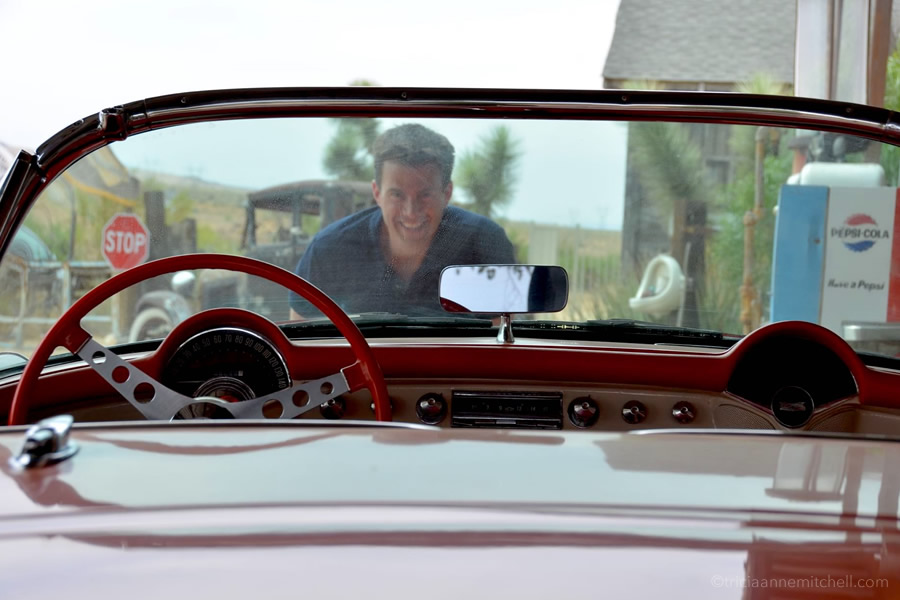 At a gas station along Route 66, a man peeks through the windshield of a vintage convertible.