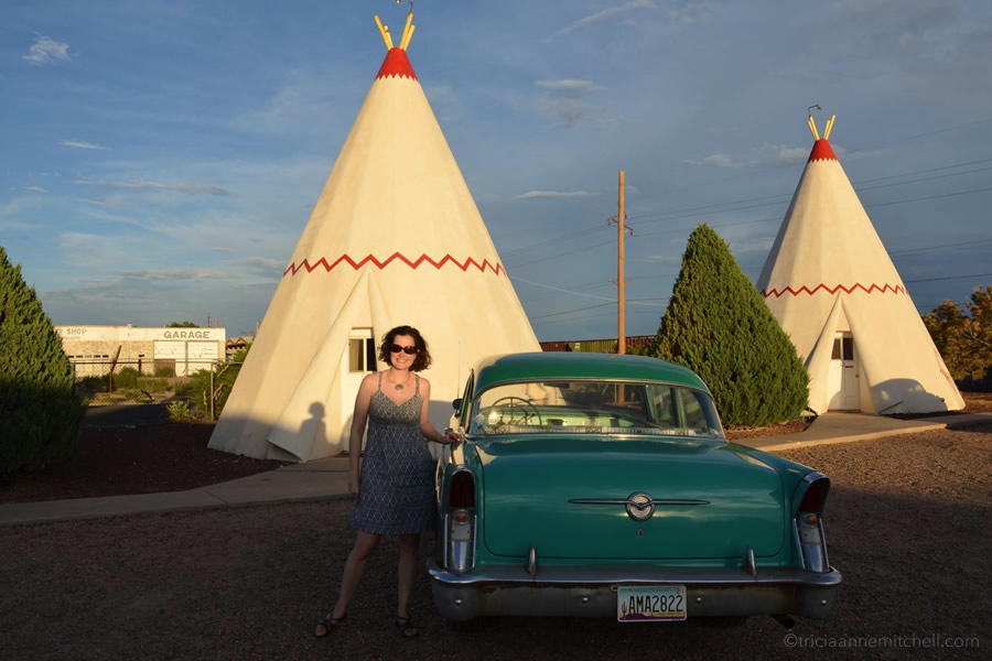 A woman poses next to a green vintage convertible at the Wigwam Motel. The complex rents out teepee style hotel rooms on the Arizona segment of Rotue 66.