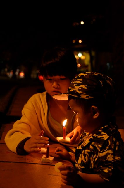 Two kids light a candle in Hoi An, Vietnam.